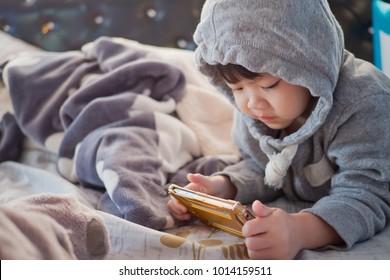chinese girl  playing smartphone. chinese child addicted phone. asian girl play smartphone. kid use telephone. watching smartphone. watching cartoon