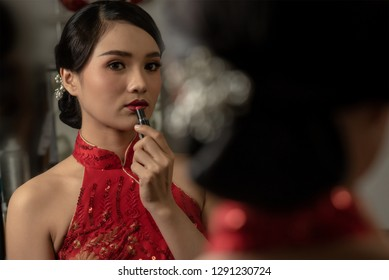 A Chinese girl is preparing to celebrate in Chinese new year festival. She is wearing a beautiful red Cheongsam and fully make up on her face. That is the meaning of elegant and cheerfulness.