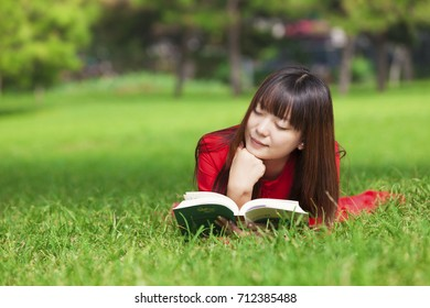 Chinese girl reading on the grass
