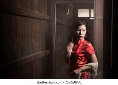 A Chinese girl in red Qipao dress with old wooden house background.