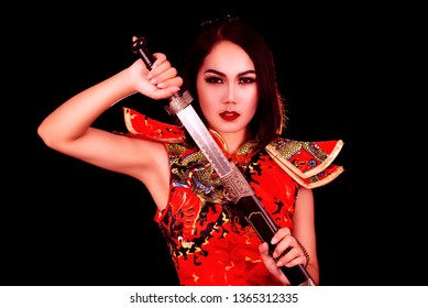 Chinese girl with a sharp sword in her hands on a black background