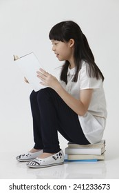 chinese girl sitting on stack of book reading
