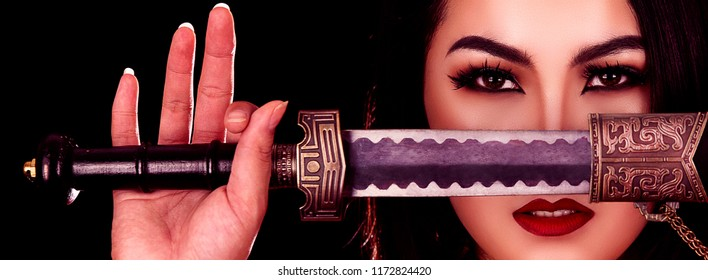 Chinese girl with a traditional suit with a sharp sword in her hands. Beautiful and belligerent face.