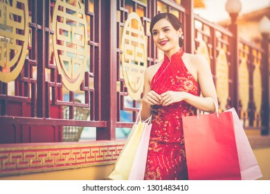 Chinese girl wearing Cheongsam and smile happily. Holding her shopping bags after a lot of shopping malls in Chinatown and was walking on the sidewalk. Amid the atmosphere of the evening sun.