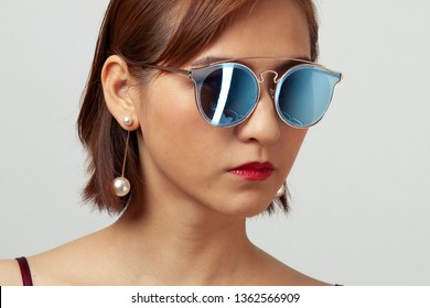 Chinese Girl wearing varies types of fashion sunglasses,looking sharp