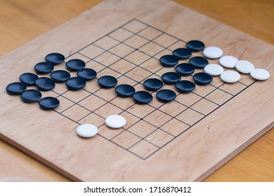 Chinese go game board, close up view of playing black and white stone pieces, Alphago