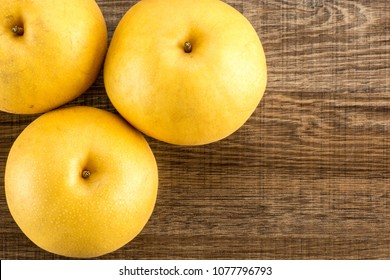 Chinese golden pears top view Nashi variety isolated on wooden background three whole round