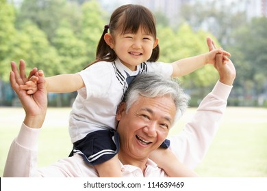Chinese Grandfather Giving Granddaughter Ride On Shoulders In Park