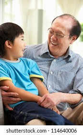 Chinese Grandfather And Grandson Relaxing On Sofa At Home