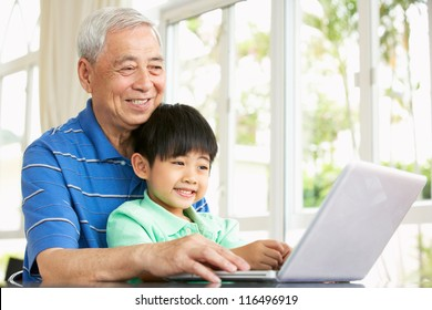 Chinese Grandfather And Grandson Sitting At Desk Using Laptop At Home