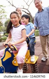 Chinese Grandparents Playing With Grandchildren In Playground