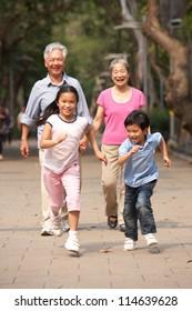 Chinese Grandparents Walking Through Park With Running Grandchildren