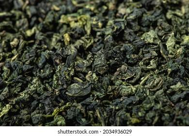 Chinesischer grüner Laubtee. getrockneter Tee hinterlässt Hintergrund. Nahaufnahme, selektiver Fokus.