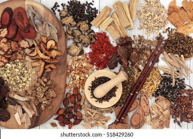 Chinese herb selection used in traditional alternative herbal medicine with mortar and pestle and chopsticks over distressed white wood background.