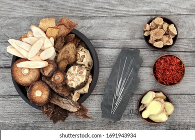 Chinese herbs and acupuncture needles used in traditional herbal medicine on rustic wood background.