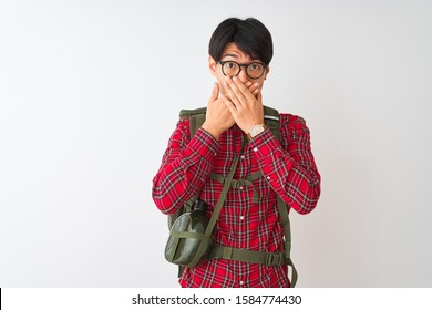 Chinese hiker man wearing backpack canteen glasses over isolated white background shocked covering mouth with hands for mistake. Secret concept.