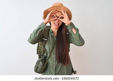 Chinese hiker woman wearing canteen hat glasses backpack over isolated white background doing ok gesture like binoculars sticking tongue out, eyes looking through fingers. Crazy expression.