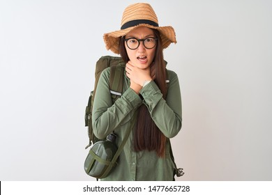 Chinese hiker woman wearing canteen hat glasses backpack over isolated white background shouting and suffocate because painful strangle. Health problem. Asphyxiate and suicide concept.