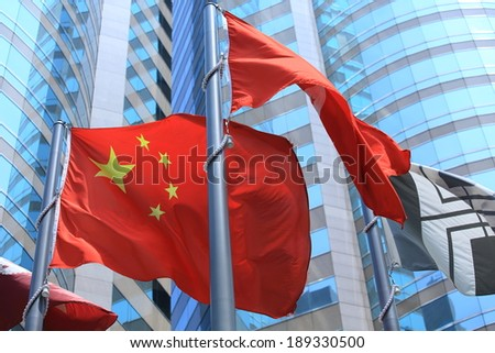chinese and hong kong flags blow in the wind with glass building background