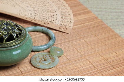 Chinese incense burner, traditional nephrite jewelry and on the bamboo mat background. still-life. copy space