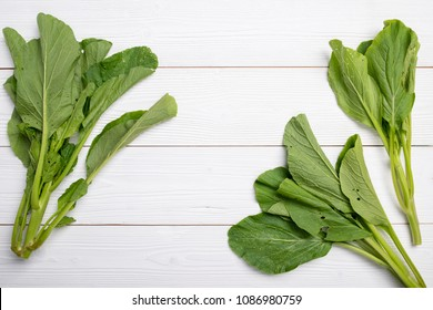 Chinese Kale or Chinese Broccoli on white wood textured background with copy space, flat lay
