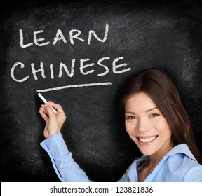 Chinese language learning. Woman teacher or student writing learn chinese on blackboard / chalkboard. Chinese Asian / Caucasian mixed race woman.