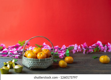 Chinese language mean rich or wealthy and happy.Accessories on Lunar New Year & Chinese New Year vacation concept background.Orange in wood basket with  red pocket money and flower on modern wooden.