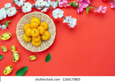 Chinese language mean rich or wealthy and happy.Top view decoration Chinese new year & lunar new year holiday background concept.Flat lay fresh orange in basket & gold money with blossom on red paper.