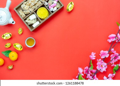Chinese language mean rich or wealthy and happy.Table top view Lunar New Year & Chinese New Year vacation concept background.Flat lay orange in wood basket & white flower on modern rustic red backdrop