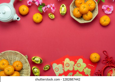 Chinese language mean rich or wealthy and happy.Table top view Lunar New Year & Chinese New Year concept background.Flat lay orange & pig doll with gold  and red pocket money card on red wallpaper.