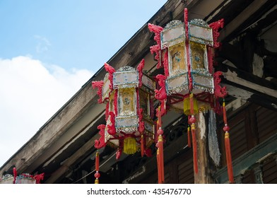 Chinese Lanterns Hanging On The Roof of Old Wood House.