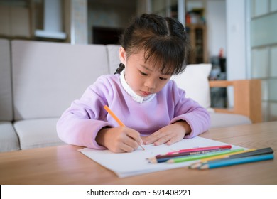 chinese little girl learn to draw on a paper with color pencil