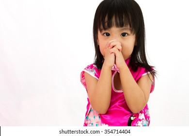 Chinese little girl wearing Cheongsam praying in plain white background.