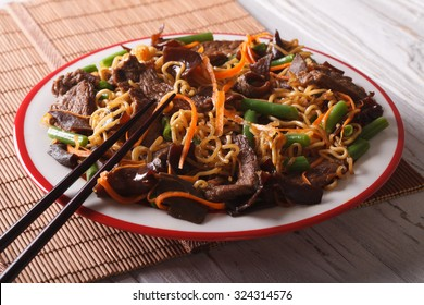Chinese lo mein with beef, muer and vegetables close-up on a plate. Horizontal