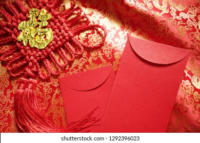 Chinese Lunar New Year celebrations theme blank red envelope and hanging decoration with golden blessing word means 'good fortune' on red and gold traditional Chinese pattern brocade fabric background