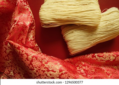 Chinese Lunar New Year celebrations theme holiday lucky food uncooked dried Longevity Noodles over red background with curly traditional brocade fabric. (close up, top view, selective focus)