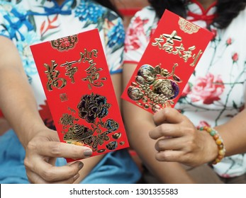Chinese Lunar New Year celebrations with red envelopes in hands of Asian women. The chinese word on left means 'everything you do will be smoothly'. Right one means 'best of luck in everything'.