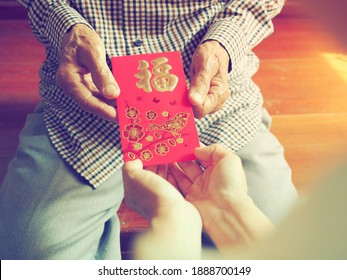 Chinese Lunar New Year celebrations theme people giving red envelope with blessing words contained money as a gift. The Chinese word means happiness or good fortune. (selective focus, vintage filter)