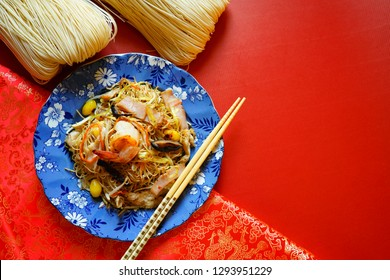 Chinese Lunar New Year lucky food stir fried noodle with shrimp, ham, mushroom, ginkgo nuts, vegetables served in blue plate with chopsticks on red background with dried noodles or Longevity Noodles.