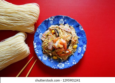 Chinese Lunar New Year lucky food stir fried noodle with shrimp, ham, mushroom, ginkgo nuts, vegetables served in blue plate on red background with chopsticks and uncooked dried longevity noodles.