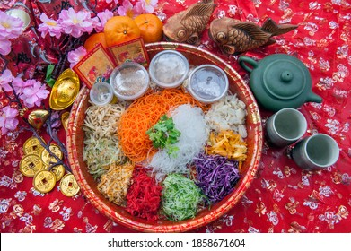 "Chinese Lunar New Year Prosperity Toss is a Cantonese-style raw fish salad Platter on red table cloth. Translation on Red packet and gold ingots ""Prosperity and good luck"""