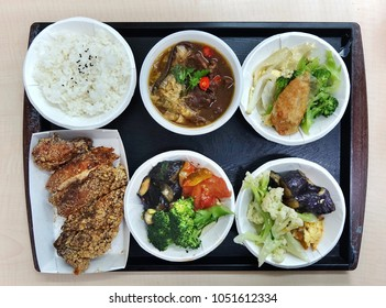A Chinese lunch set with fried chicken, beef stew and assorted vegetables