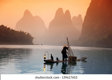 Chinese man fishing with cormorants birds, Yangshuo, Guangxi region, traditional fishing use trained cormorants to fish