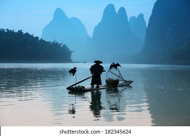 Chinese man fishing with cormorants birds, traditional fishing use trained cormorants to fish, China