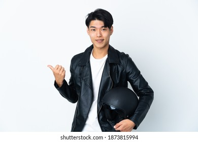 Chinese man with a motorcycle helmet isolated on white background pointing to the side to present a product