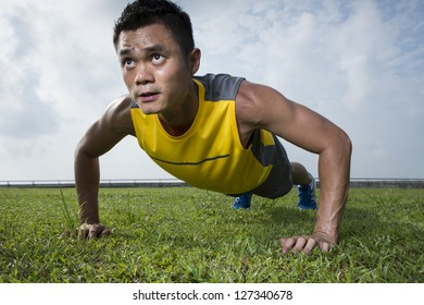 Chinese man performing push up in the city park. Male fitness concept.