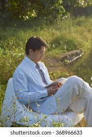 Chinese man reading book outdoor in morning