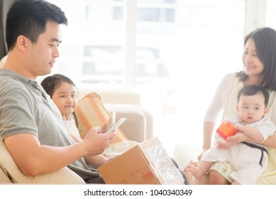 Chinese man scanning QR code with smart phone. Happy Asian family at home, natural living lifestyle indoors.