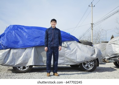 Chinese man standing next to covered car