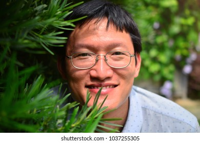 Chinese man wearing eye glasses with natural green plant background.